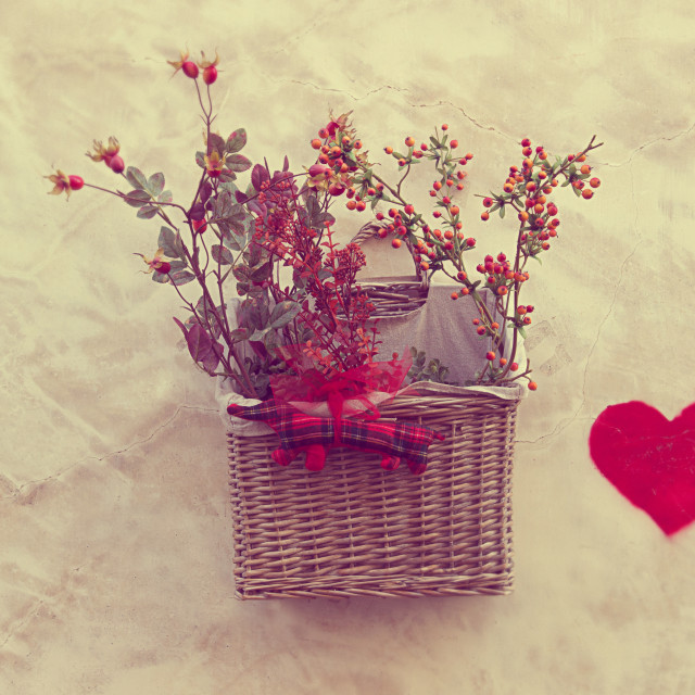 """""""Wicker basket with plants attached to a wall and a red heart drawn"""" stock image"""