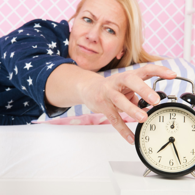 """Woman put out the alarm clock"" stock image"