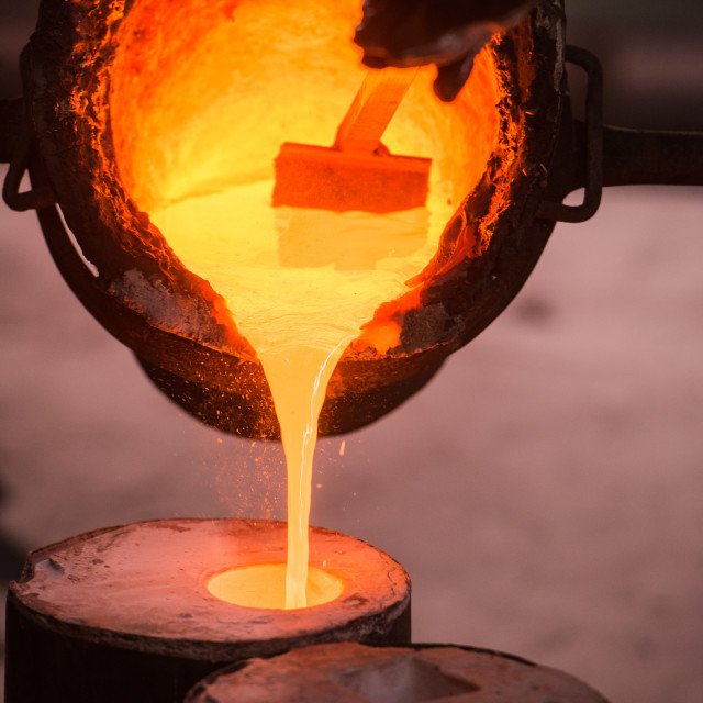 """Foundry worker pouring hot metal into cast"" stock image"