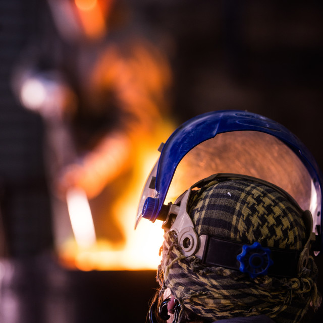 """""""Steel worker in protective clothing raking furnace in an industr"""" stock image"""