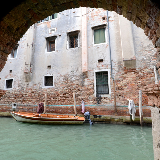 """Single small boat framed by doorway, Venice Italy"" stock image"