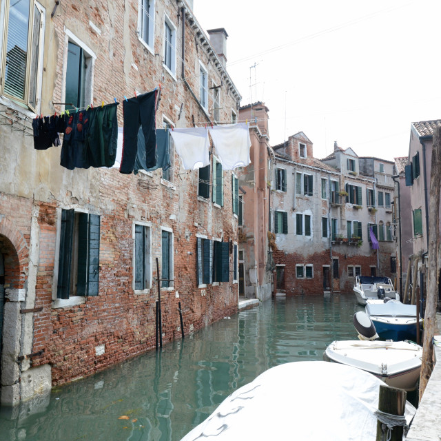 """Clothes hung to dry over calm canal in Venice, Italy"" stock image"