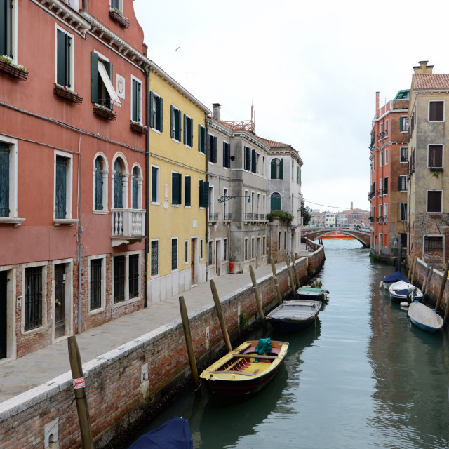 """Yellow boat on small canal in Venice, Italy"" stock image"