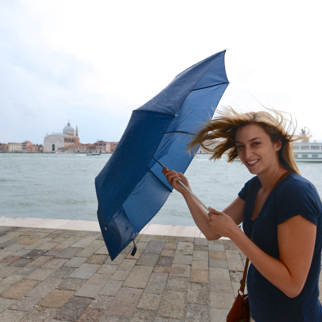 """Woman fights wind with umbrella in Venice, Italy"" stock image"