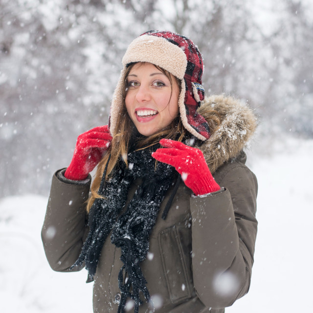 """""""girl smiling in the snow wearing a lumberjack hat"""" stock image"""