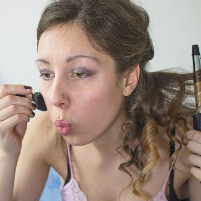 """Girl straightening her hair and putting on makeup"" stock image"