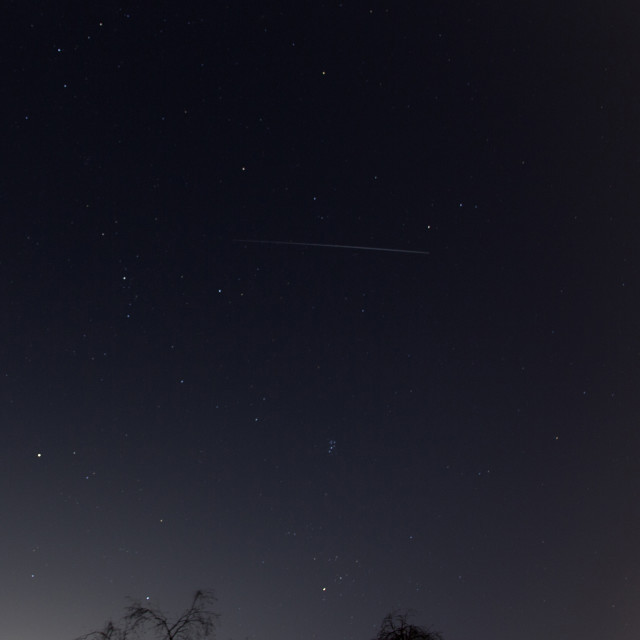 """Purple sky stars plane trail"" stock image"