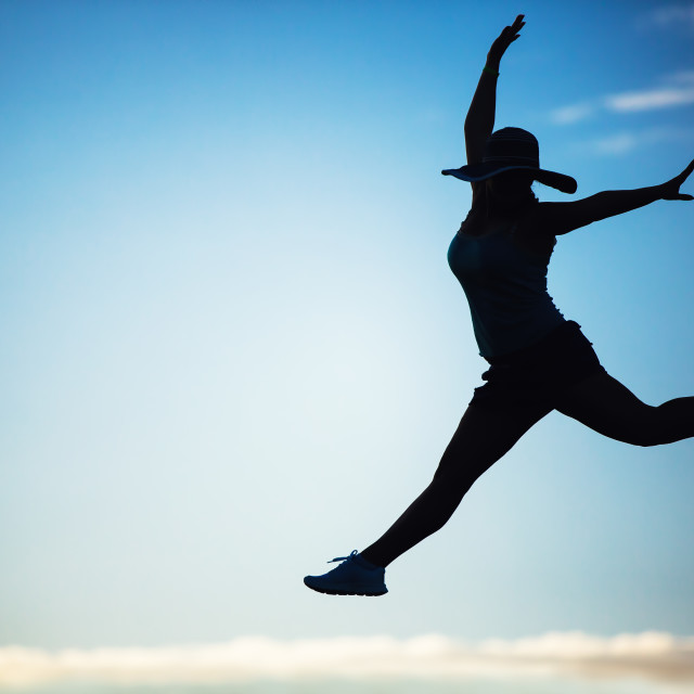 """""""Silhouette of a beautiful girl jumping over sunset"""" stock image"""