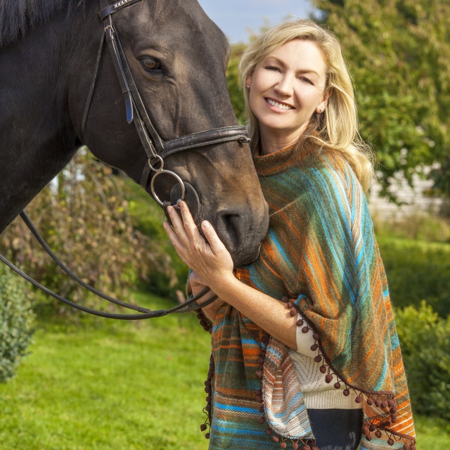 """""""Woman in Poncho Leading Her Horse"""" stock image"""