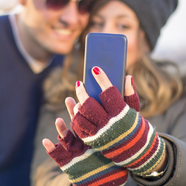 """Couple taking selfie outdoors waring Christmas hats"" stock image"