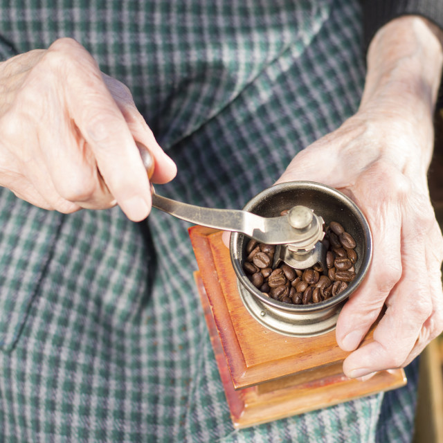 """""""Old hands grinding coffee on a vintage coffee grinder"""" stock image"""