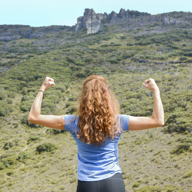 """""""girl flexing muscles on a mountain top"""" stock image"""
