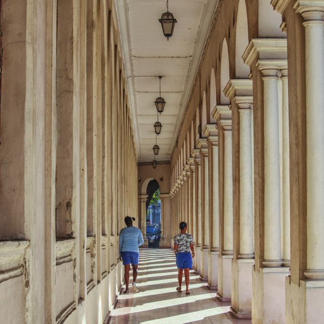 """Two girls walking in an arched hallway"" stock image"
