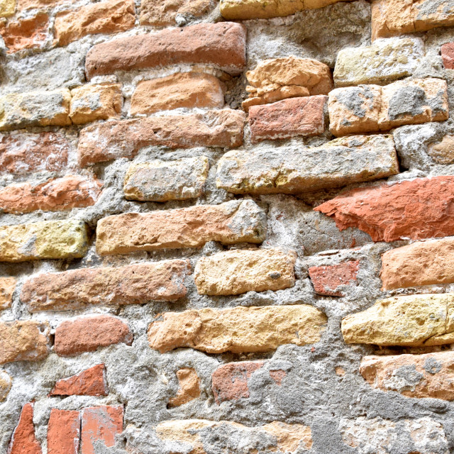 """Brick wall is worn and textured by weather"" stock image"