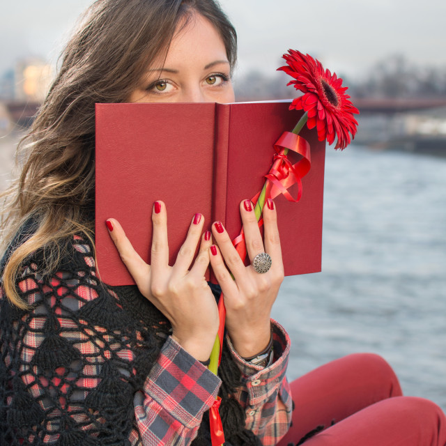 """Brunette girl with a book by the river bank"" stock image"