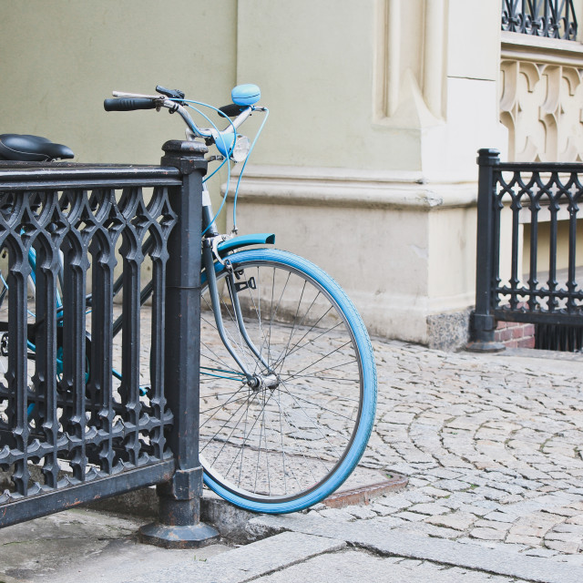 """""""Vintage blue bicycle locked on fence in a city"""" stock image"""