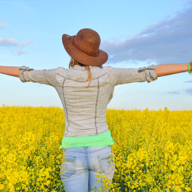 """Girl embracing a field of yellow flowers"" stock image"