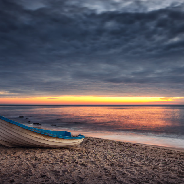 """Boat and sunrise with dramatic cloudscape"" stock image"