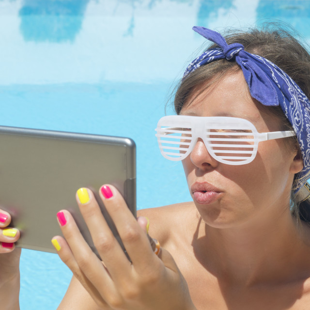 """""""Young girl making selfie by the pool with a tablet wearing rave"""" stock image"""