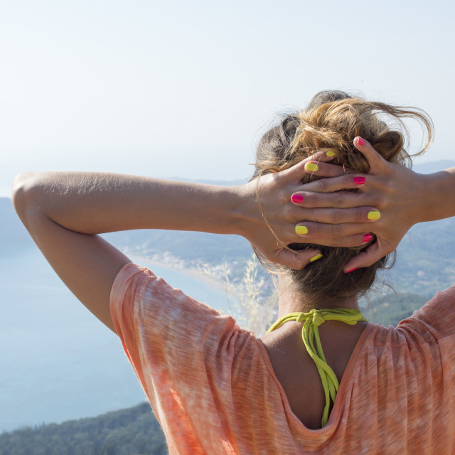 """Girl facing the extraordinary view at the seaside from mountain"" stock image"