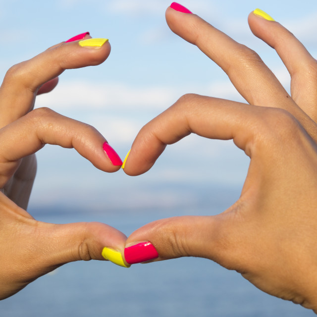 """Heart shape made of woman hands against sea and sky"" stock image"