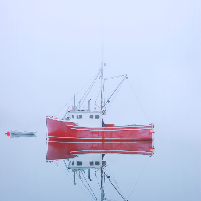 """Red Fishing boat on misty lake"" stock image"