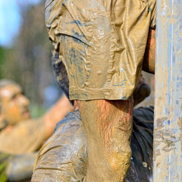 """Sportsman's legs in dirty sportswear climbing"" stock image"