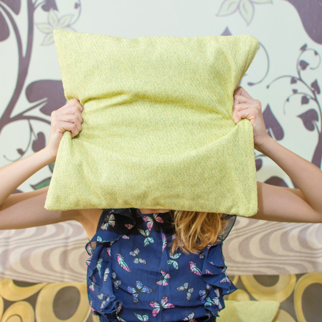 """girl hiding behind a pillow"" stock image"