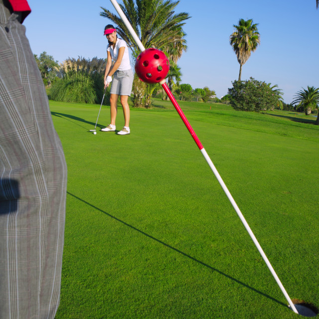 """""""golf woman putting gol ball and man holds flag"""" stock image"""
