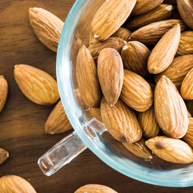 """Almond in a transparent cup on a wooden table"" stock image"