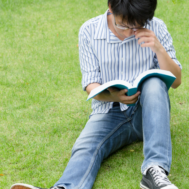 """Young asian man reading a book on grass"" stock image"