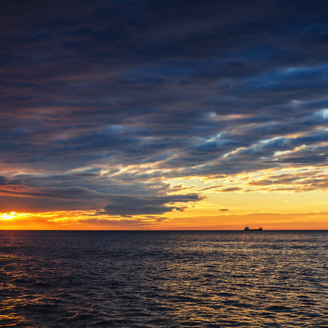 """""""Sun setting at the sea with sailing cargo ship, scenic view"""" stock image"""
