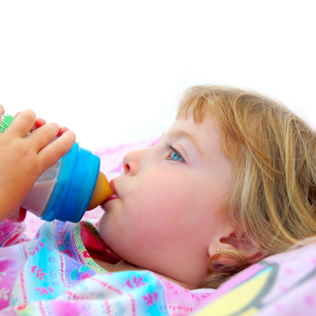 """""""girl drinking bottle of milk laying on bed"""" stock image"""