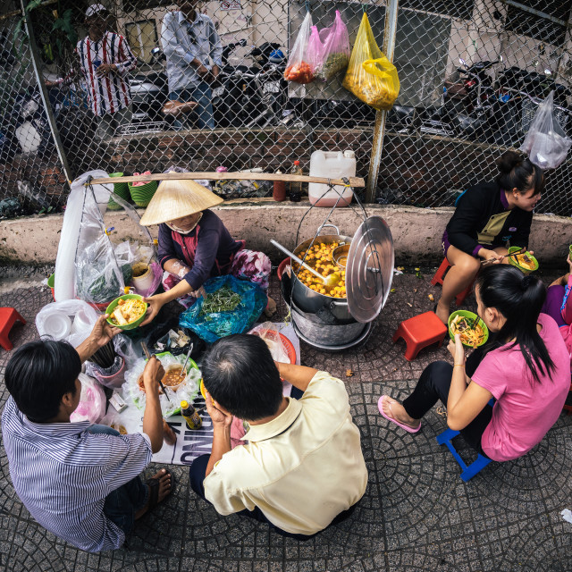 """Vietnamese having meal in front of the street food vendor: typical lifestyle"" stock image"