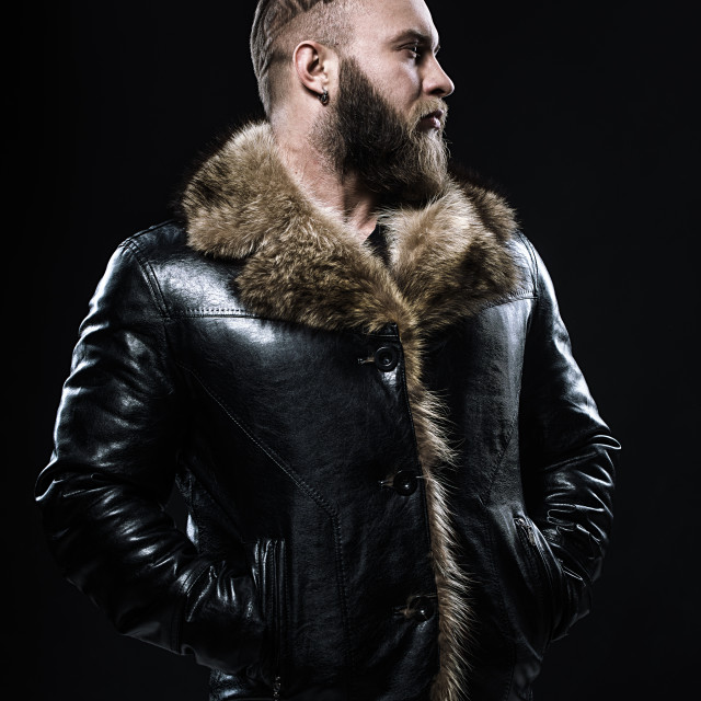 """Brutal handsome unshaven man with long beard and moustache in black fur coat with collar."" stock image"
