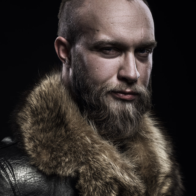 """Brutal handsome glum unshaven man with long beard and moustache in black fur coat with collar."" stock image"