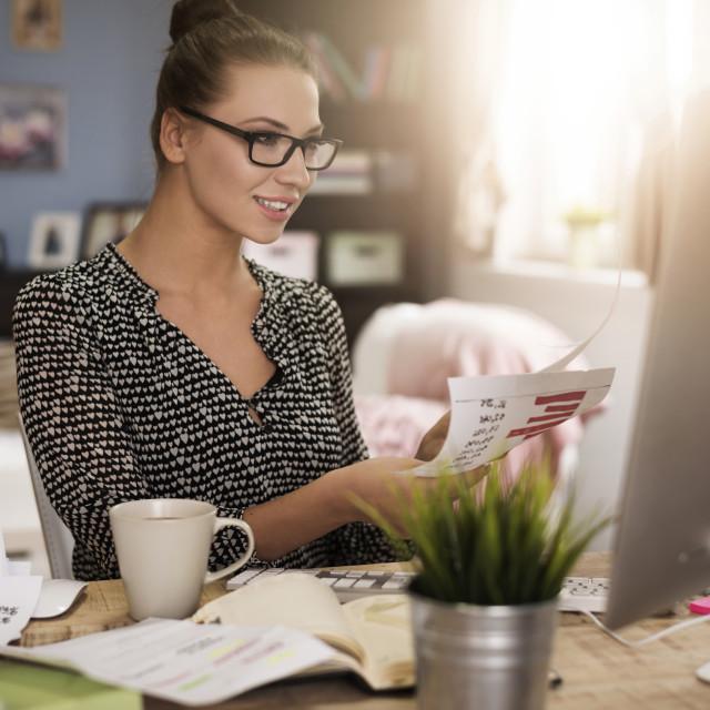"""Hardworking woman analysing important documents"" stock image"