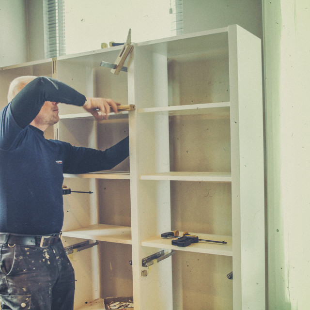"""Carpenter building a bookcase"" stock image"