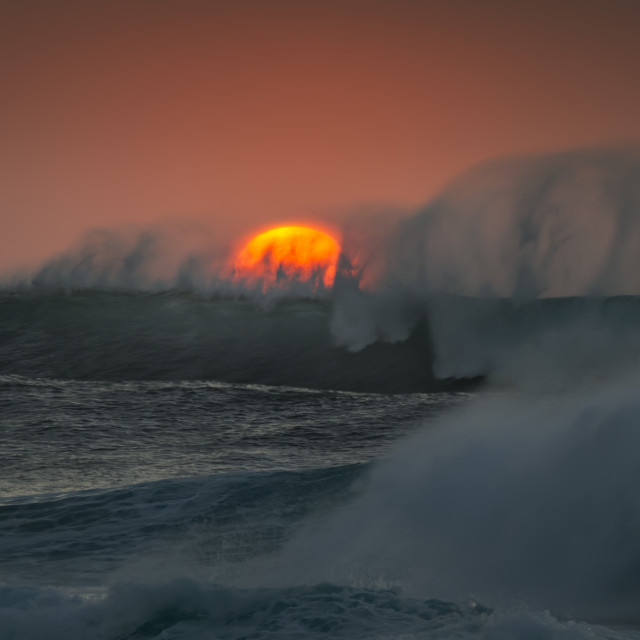 """The Sun setting behind a large Ocean Wave"" stock image"