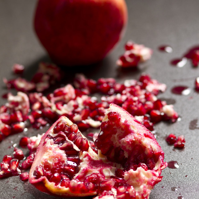 """Crushed pomegranate with a whole fruit on a dark background"" stock image"