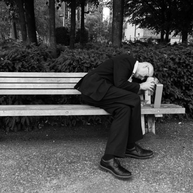 """Man sleeping on bench"" stock image"