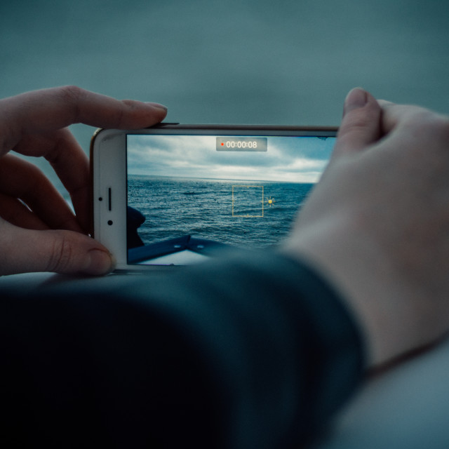 """Filming the ocean on an iPhone"" stock image"