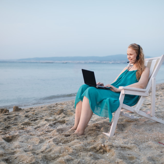 """Woman talking skype at the beach"" stock image"