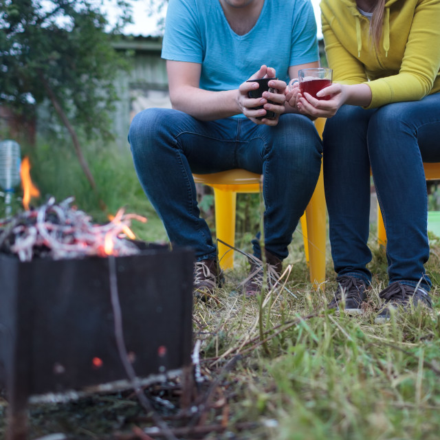"""""""Couple with tea cups in hands near the smouldering fire"""" stock image"""