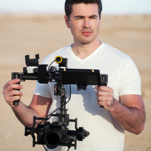 """""""Videographer with steadicam equipment on the beach"""" stock image"""