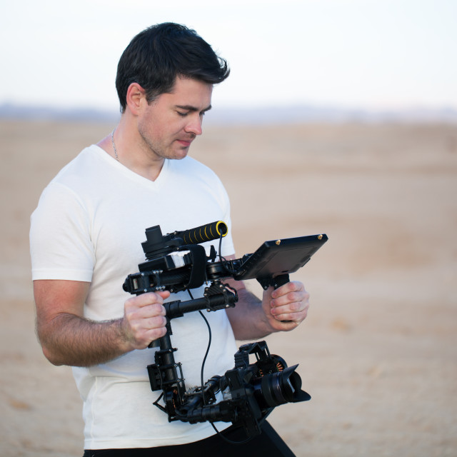 """""""Young man using steadycam for shooting on beach"""" stock image"""