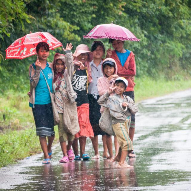 """""""Children walk down wet road"""" stock image"""
