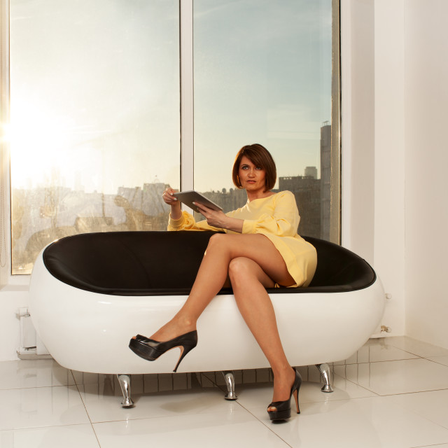 """Elegant businesswoman sitting on sofa with crossed legs"" stock image"