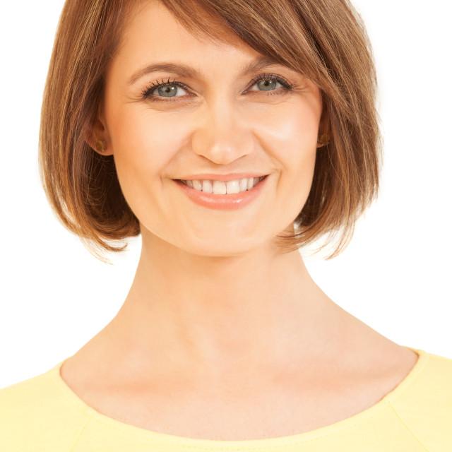 """Headshot of beautiful woman in yellow smiling at camera"" stock image"