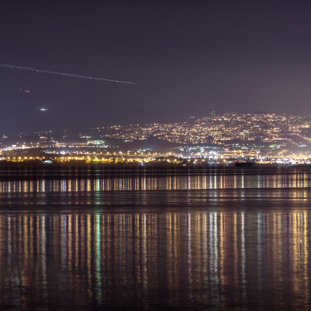 """Light streak in sky over city at night"" stock image"